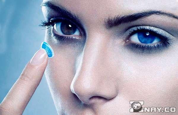 Вставляет в глаз голубую линзу
