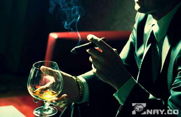 Пьет с сигарой из бокала