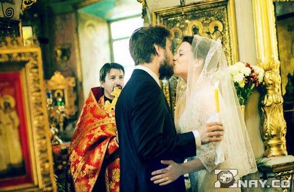 Пара целуется в церкви