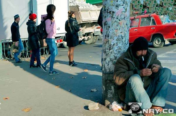 Бездомный сидит и попрошайничает