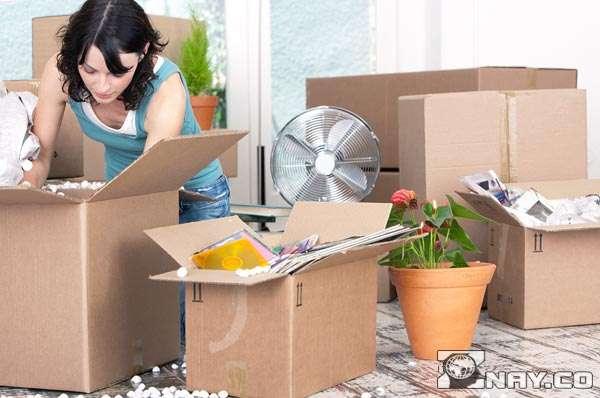 Девушка складывает коробки, собираясь переезжать