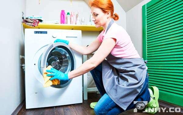 Протирает стиральную машину в доме