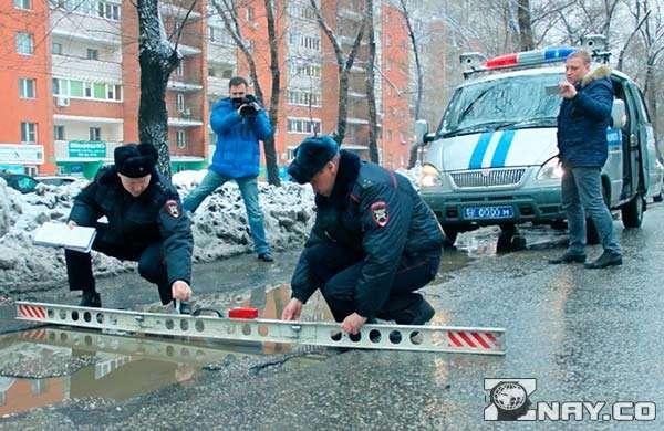 Приехали по жалобе на дорогу, измеряют ямы