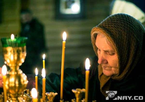 Бабушка ставит пасхальные свечи