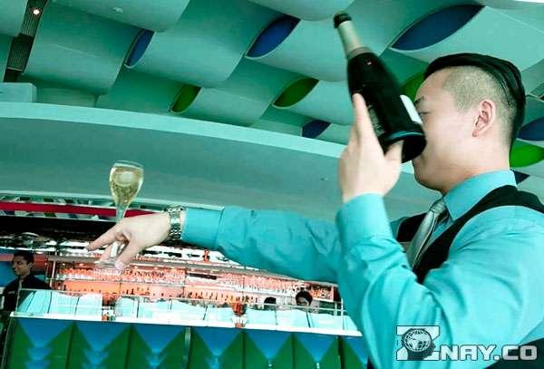 Бармен держит бутылку вина за дно