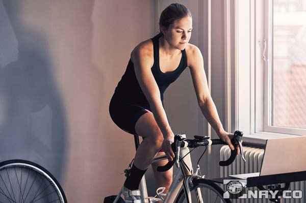 Тренируется в комнате на вело