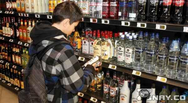 Ребенок рассматривает бутылку водки